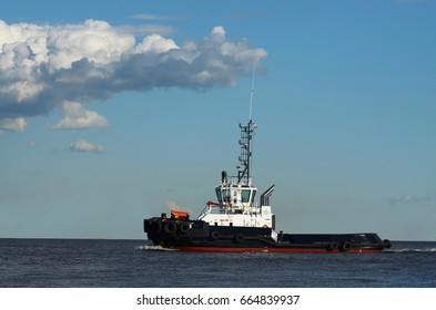 Port tow boat floats on the sea on background of blue sky.