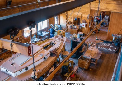 Port Townsend, Washington / United States - April 20, 2019: a single craftsman at work in the Wooden Boat Foundation shop in Port Townsend, Washington. A sailboat sits in the shop partially completed