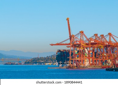 Port of Vancouver view from coal harbor, cranes in red at an industrial port with a bridge in the back. Selective focus, street view, travel photo. Vancouver, BC, Canada-September 29,2020.