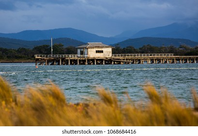 PORT WELSHPOOL, VICTORIA, AUSTRALIA - 06 APRIL 2018: Remnant structure of the derelict Long Jetty at Port Welshpool in Corner Inlet, stark against Wilsons Promontory National Park in the distance.