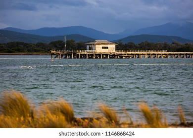 PORT WELSHPOOL, VICTORIA, AUSTRALIA - 06 APRIL 2018: The ruins of the old Long Jetty in Corner Inlet with the distant peaks of Wilsons Promontory National Park in the background.