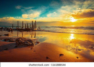 Port Willunga beach view with jetty pylons in the water at sunset,  South Australia