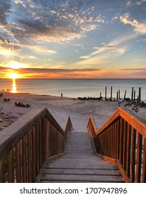 PORT WILLUNGA, SOUTH AUSTRALIA,DECEMBER 2019; sunset from the stairs overlooking the old jetty and beach goers by the water