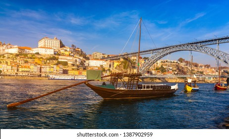 Port wine boats at the waterfront with Dom Luis bridge and the old town on the Douro River in Ribeira in the city centre of Porto in Porugal in Europe. Portugal, Porto