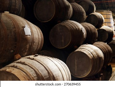 Port wine from the vineyards Douro Valley in Portugal aging in oak barrels stacked in the old traditional dark cellar. Product of organic farming.