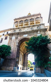 Porta Nuova (New Gate) is a monumental city gate of Baroque style with people around located in the old town of Palermo in Sicily, Italy