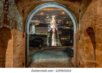 Porta San Giacomo illuminated at night with a view of lower Bergamo