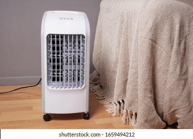 portable air cooler and humidifier on casters in domestic living room to improve indoor clmate