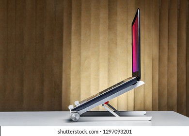 Portable aluminum alloy stand bracket support holder for laptop  set up with notebook on desk.