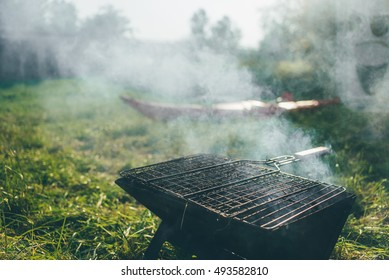 Portable bbq on fire at a camping