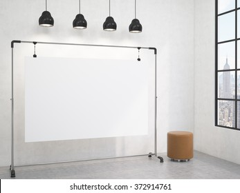 portable blank white board in the corner of the room, window with a city view to the right, brown pouffe to the right, four black lamps above. Concept of demonstration. 3D rendering