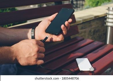 Portable charger in the hands of a person. Powerbank charges the phone