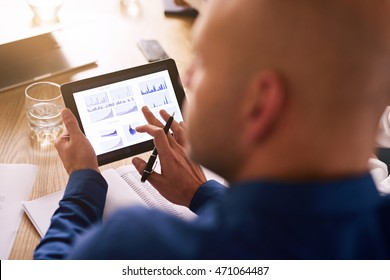 Portable computer tablet being used by a caucasian male business executive during a board meeting to view live analysis of the company's investment portfolio.