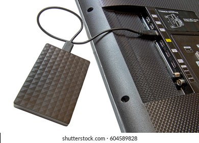 The portable drive is plugged into a slot in the back of the TV. Close-up view of copying data from the television.