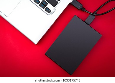 A portable hdd connected to a laptop on a red background, top view. The concept of data storage