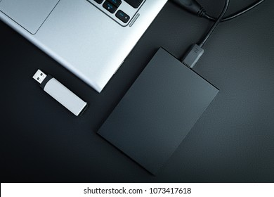 A portable hdd connected to a laptop with usb flash drive on a black table, flat lay. The concept of data storage