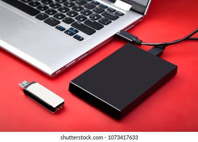 A portable hdd connected to a laptop with usb flash drive on a red table. The concept of data storage
