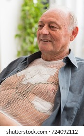 Portable holter for cardiac monitoring of electrical activity of the cardiovascular system attached to a male senior patient's chest during a 24 hour diagnostics process