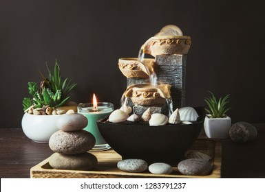 Portable indoor fountain for good Feng Shui in Your Home concept. Portable indoor small tabletop fountain. Spiritual mind and soul balance concept. Green plants in flower pot on background.