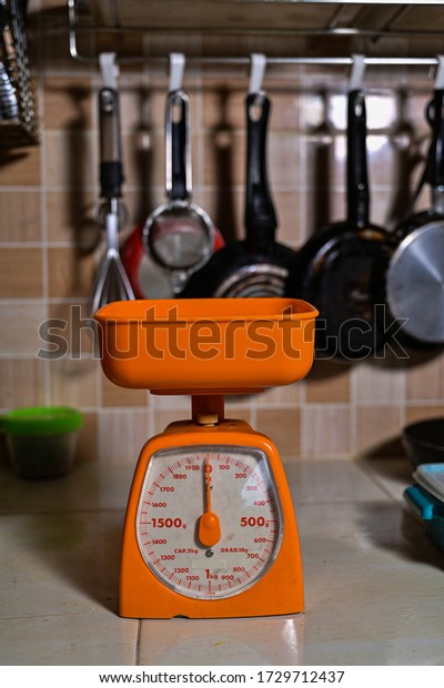 Portable kitchen balance scales for measuring the weight of baking and food ingredients with daily used kitchen ware background