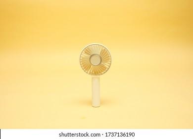 Portable mini fan on a yellow background