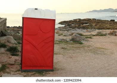 portable red toilet in the beach at sunset