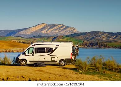 Portable solar panel at camper van camping on nature, lake Embalse del Guadalhorce, Ardales Reservoir, Malaga province in Andalusia, Spain.