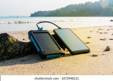Portable solar panel is on the beach in the sand and charges the battery of the mobile phone. use of solar energy in the wild on a desert island. Modern frameless smartphone