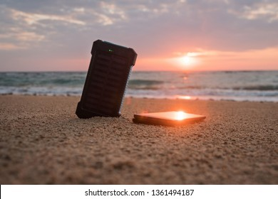 Portable solar panel is on the beach in the sand and charges the battery of the mobile phone. beautiful tropical sunset or sunrise