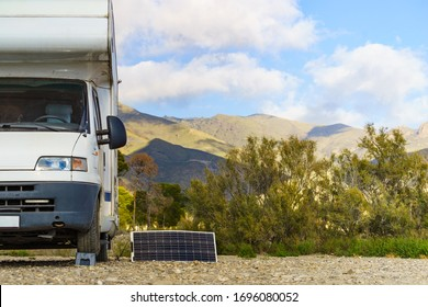 Portable solar photovoltaic panel, charging battery at camper car rv. Sierra Alhamilla mountain range landscape.