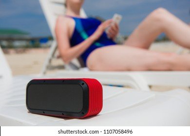 Portable speaker and female with mobile phone