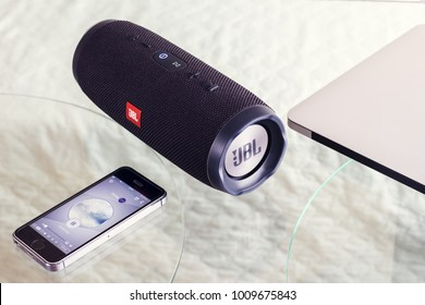 portable speaker JBL Reharge 3 on a glass table produces music from the iPhone - January 16, 2018