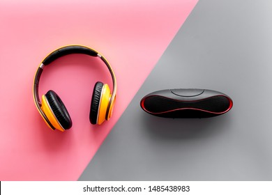 Portable speakers and headphones as gadgets for listen to the music on pink and gray background top view