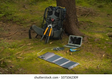 portable technology, solar panel, tablet, laptop and backpack in a birch forest