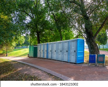 Portable washrooms in nature. Long row of portable bio toilet cabins in Moscow park. Line of chemical toilets for the holiday, festival. WC.