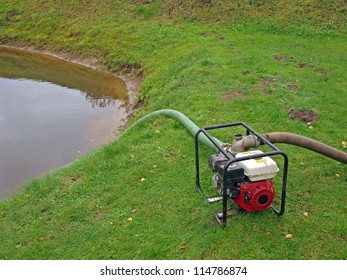 Portable water pump on country pond coast