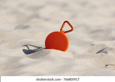 Portable wireless speaker on the beach