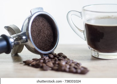 Portafilter with coffee bean and cup of coffee.
