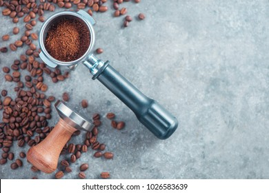 Portafilter with ground coffee, tamper, and coffee beans on a concrete background with copy space. Barista concept from above.
