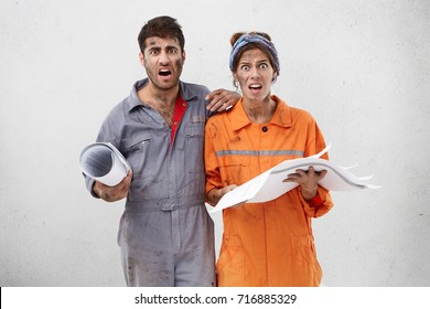 Portait of astonished nervous female and male maintenance workers or carpenters look with unhappy expression, hold blueprint in hands, isolated over white background. Occupation and teamwork concept