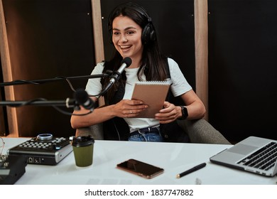 Portait of attractive young female radio host holding a script, looking emotional while speaking in microphone, moderating a live show