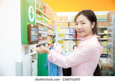 Portait of beautiful asian woman in pink dress sac using  self-service barcode scanner in shopping mall