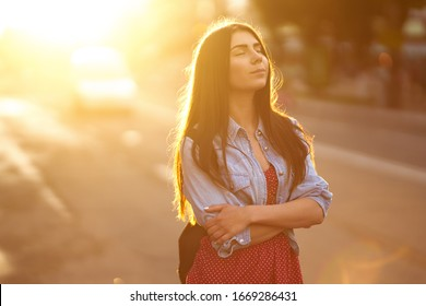 Portait of beautiful young woman at sunset. Young girl enjoys the sunshine on a city street.  People, lifestyle, travel and vacations concept.