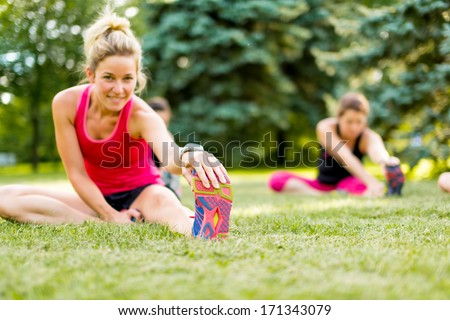 Portait of a blond girl getting streching her legs before running outdoors