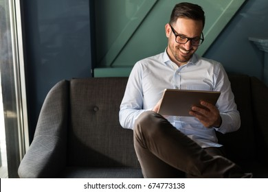 Portait of businessman in glasses holding tablet