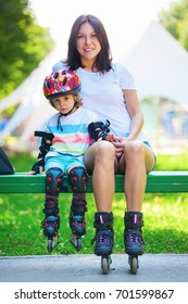 Portait of cute baby boy and his mom wearing inline skates sitting on bench in the park.