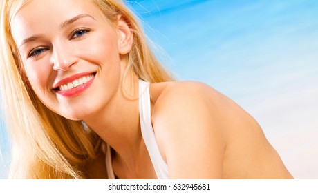 Portait of happy smiling cheerful young beautiful blond woman on the beach