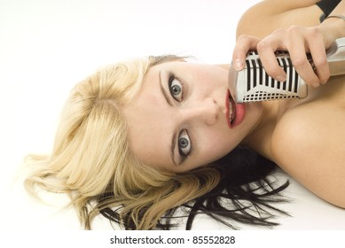 Portait of pretty woman or girl music singer lying down with microphone on white