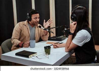 Portait of two radio hosts, man and woman talking with each other while moderating a live show in studio