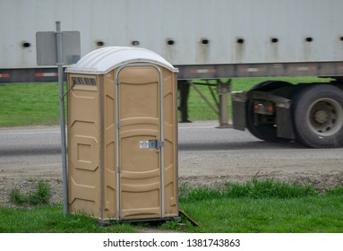 Portapotty on a roadside with truck passing